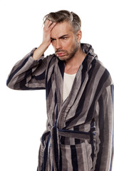 handsome hungover man in a striped bathrobe