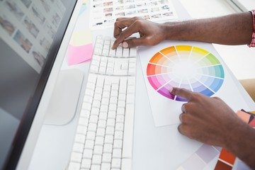 Designer using a colour wheel and typing on keyboard