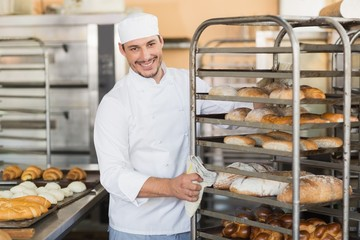 Smiling baker pushing tray of bread