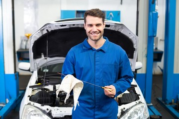 Mechanic testing oil in car