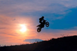 Fototapety Extreme sports background  silhouette of biker jumping motocross