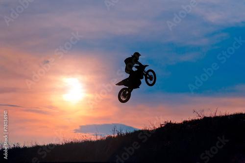 Foto op Plexiglas Motorsport Extreme sports background silhouette of biker jumping motocross