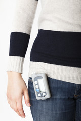 Young woman with diabetes using insulin pump to keep costant the