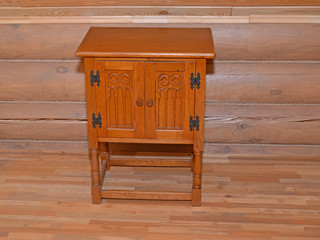 The wooden bedside table stands near a timbered wall