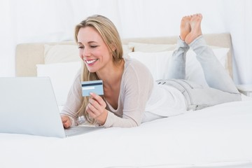 Cheerful blonde shopping online on the bed