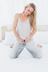 Blonde forcing to close her jeans on the bed