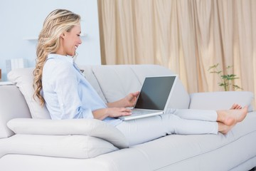 Smiling blonde relaxing on couch with her laptop