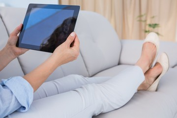 Woman sitting on couch using tablet pc