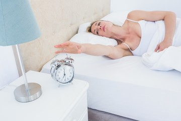 Blonde woman lying in bed reaching for alarm clock