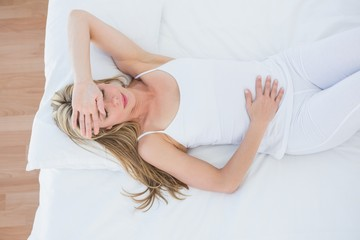 Blonde woman lying suffering from stomach pain
