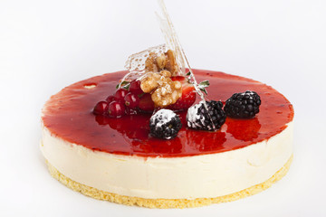 Cheese cake with strawberry jam and blackberries a white backgro