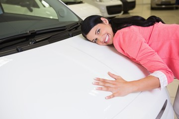 Smiling woman hugging a white car