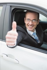 Businessman smiling at camera showing thumbs up