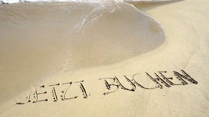 Text jetzt buchen in Sand gezeichnet wird von Wellen weggespült
