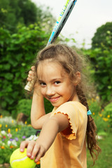 portrait of cute little girl playing tennis outdoors