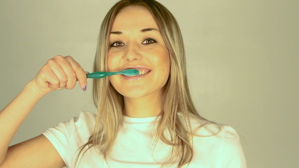 healthy young woman brushing teeth in bathroom