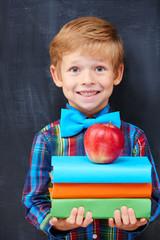 Smiling encoureged ginger boy holding a pile of books