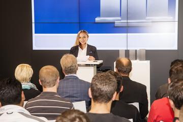 Junge Frau am Rednerpult vor Publikum