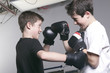 young boy with black boxing gloves fight with is brother - 78046761