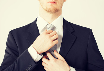 man adjusting his tie