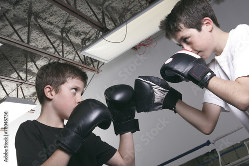 Foto op Canvas Stadion young boy with black boxing gloves fight with is brother