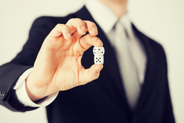 mans hand holding white casino dice