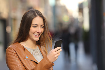 Happy woman using a smart phone in the street