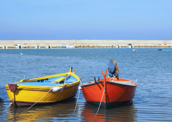 Red and yellow rowing boat in Mediterranean water