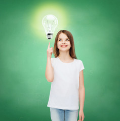 smiling school girl pointing finger to light bulb