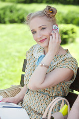 Pretty woman in retro style sitting in park with mobile phone