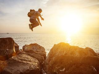 traveler man jumping over rocks in sunset