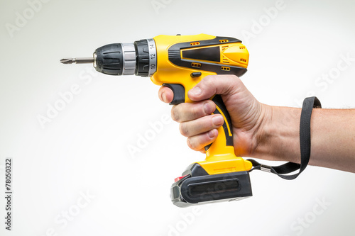 electric screwdriver in his hand - 78050322