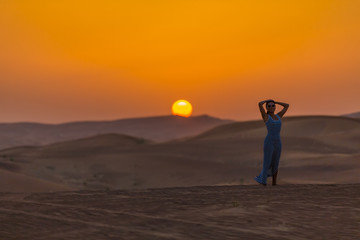 girl in the desert on a background of a sunset