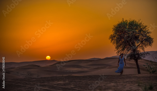 In de dag Oranje eclat girl in the desert on a background of a sunset