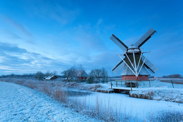 Dutch windmill on snow in winter dusk