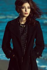 Emotive portrait of beautiful brunette in black coat