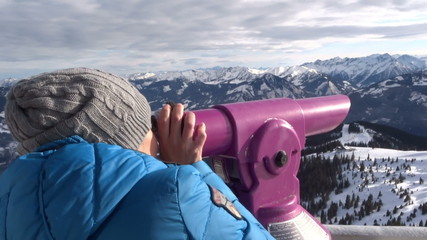 Woman looking through telescope at viewpoint in the mountains