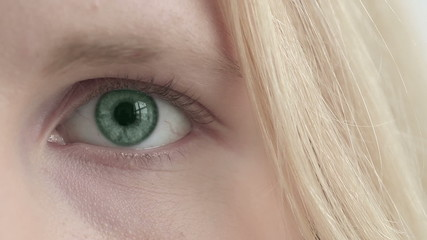 Eye of blonde girl changes color. Close up