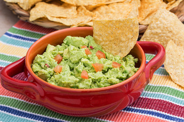 Chunky homemade guacamole in red ceramic dish
