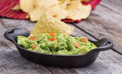 Chunky homemade guacamole in cast iron dish