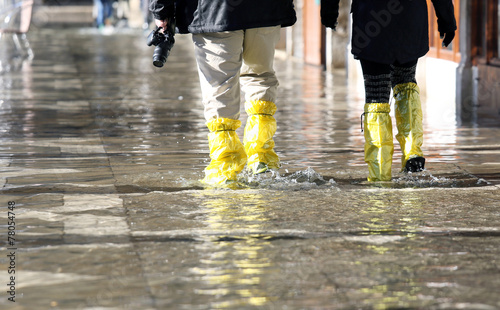 Leinwandbild Motiv venice photographer with gaiters at high tide