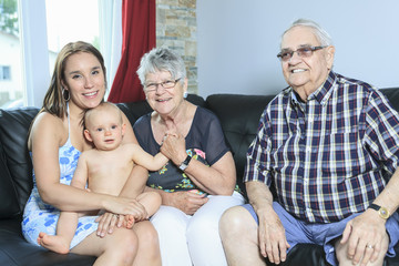 Portrait of happy mature couple with daughter and granddaughter