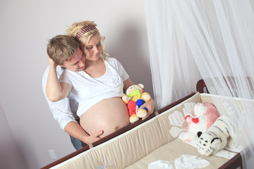 A pregnant woman with his boyfriend on the baby room