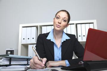 Frau im Büro macht eine Notiz