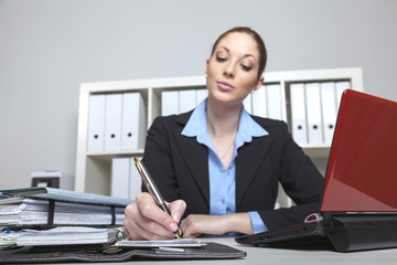 Frau im Büro trägt Termin ein