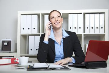 Frau telefoniert am Arbeitsplatz im Büro