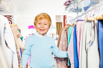 Happy blond boy laughing in shopping mall