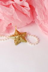 Decorative star, pearl beads and pink pom pom.