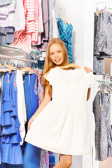 Smiling girl holds beautiful white dress on hanger