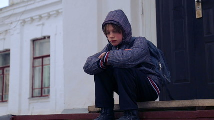 Caucasian boy near the building of the village school.